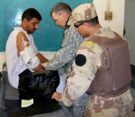 An American doctor treats an Iraqi civilian with a broken arm.