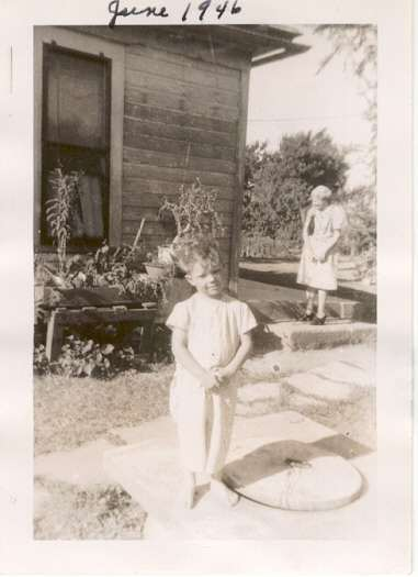 Four year old Kirk poses near the farm house where he was born as was his father.  Grandmother Wood is on the porch step.