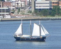 A three mast sailboat travels through Halifax harbor.