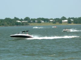 Speed boats racing across the lake on a sunny day.