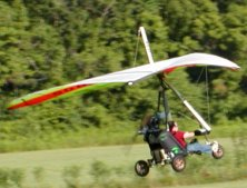 A powered hang-glider arrives.